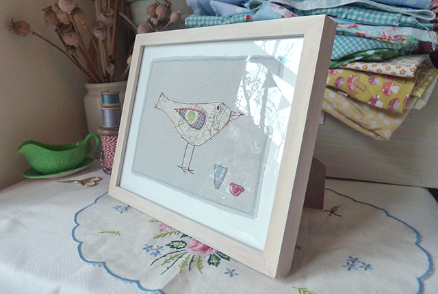 large framed textile picture of a bird made from stitched map with two cups