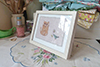 medium sized framed textile picture of a cat and a bird holding a flower
